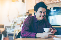 Young asian handsome businessman smiling while reading his smart. Phone with a cup of coffee in coffee cafe. Portrait of asian business man reading message with royalty free stock image