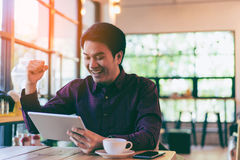 Young asian handsome businessman smiling while reading his table. Young asian handsome businessman smiling cheering while reading his tablet with a cup of coffee stock photography