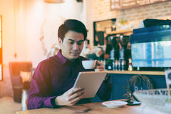 Young asian handsome businessman smiling while reading his table. T with a cup of coffee and smartphone in coffee cafe. Portrait of asian business man reading stock photo