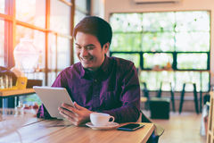Young asian handsome businessman smiling while reading his table. T with a cup of coffee and smartphone in coffee cafe. Portrait of asian business man reading stock images