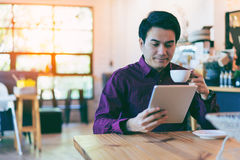 Young asian handsome businessman smiling while reading his table. T with a cup of coffee and smartphone in coffee cafe. Portrait of asian business man reading royalty free stock photography