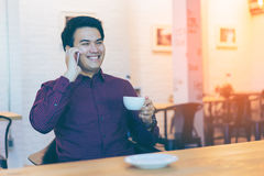 Young asian handsome businessman smiling while using his smartph. One with a cup of coffee. Portrait of asian business man using smart phone in coffee shop royalty free stock photos