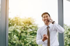 Young asian handsome businessman talking on phone and happiness stock image
