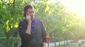 Young Asian handsome man talking on the phone in the summer sunny Park. Young Asian man talking on the cell smart phone in the summer Park. sun is shining stock video footage