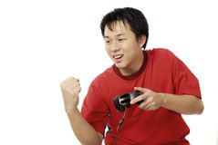 YOUNG ASIAN HAPPY WITH HIS WIN PLAYING ELECTRONIC GAMES Royalty Free Stock Photo