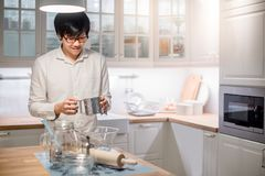 Young Asian man standing by counter in kitchen. Young Asian happy man standing in front of counter in kitchen preparing cooking wares for meal Royalty Free Stock Images