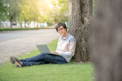 Young Asian man using laptop in the garden. Young Asian happy man using laptop computer in the garden, male university student relaxing outdoor, education and Stock Photos