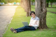 Asian man student using laptop in the garden. Young Asian happy man using laptop computer white sitting on grass in the garden. Male university student relaxing Stock Images