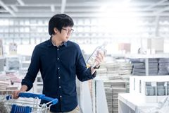 Young Asian man shopping with trolley cart in warehouse. Young Asian happy man using trolley cart choosing empty bottle. Shopping home improvement stuff in Stock Image