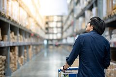 Young Asian man shopping with trolley cart in warehouse. Young Asian happy man using trolley cart putting cardboard box inside. Shopping furniture in warehouse Stock Photos