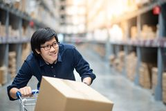 Young Asian man shopping with trolley cart in warehouse. Young Asian happy man using trolley cart putting cardboard box inside. Shopping furniture in warehouse Stock Photo
