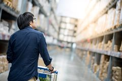 Young Asian man shopping with trolley cart in warehouse. Young Asian happy man using trolley cart putting cardboard box inside. Shopping furniture in warehouse Royalty Free Stock Images
