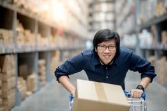 Young Asian man shopping with trolley cart in warehouse. Young Asian happy man using trolley cart putting cardboard box inside. Shopping furniture in warehouse Royalty Free Stock Photography