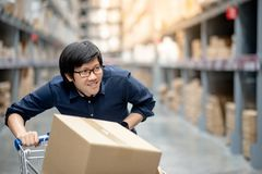Young Asian man shopping with trolley cart in warehouse. Young Asian happy man using trolley cart putting cardboard box inside. Shopping furniture in warehouse Royalty Free Stock Photos