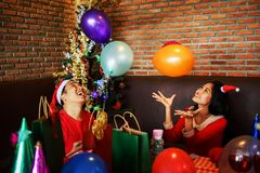 Couple celebrate Christmas party with balloon. Young Asian happy men and women couple with Santa hats play and throw colorful toy balloons for christmas and new Royalty Free Stock Photos