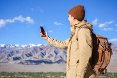 Young Asian hiker using a smartphone on top of mountain peak in Leh, Ladakh, India Stock Images