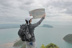 Young Asian hipster man with bag exploring map on viewpoint of mountain. Travel and adventure concept. Young Asian hipster man with bag exploring map on stock images
