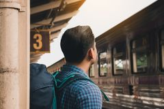 Young asian hipster man standing and waiting train on platform stock photos