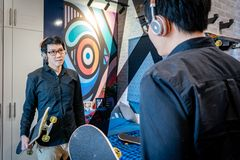 Asian hipster man holding skateboard in bedroom. Young Asian hipster and skateboarder man with headphones and eyeglasses holding skateboard looking into the Royalty Free Stock Image
