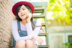Young asian hipster woman sitting and talking on phone Royalty Free Stock Image