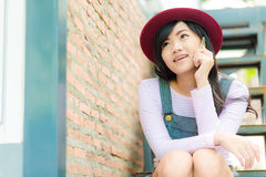 Young asian hipster woman sitting and talking on phone Royalty Free Stock Photos