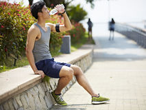 Young asian jogger resting and drinking water Stock Photo