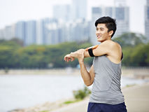 Young asian jogger stretching arms before running royalty free stock image