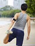 Young asian jogger stretching leg before running stock photography