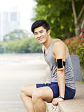 Young asian jogger taking a break stock images