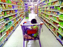 Young asian kid riding a grocery cart stock photography