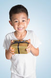 Young Asian kid in sleepwear holding a gift Royalty Free Stock Image