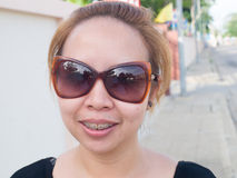 Young Asian lady wearing sunglasses smiling in nature Stock Images