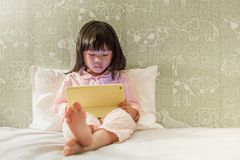 Young little girl in pyjamas playing tablet on the bed. Young asian little  girl 4 adcc79166
