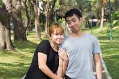 Young Asian love couple relax after an excercise in the park by playing to each other with emotion of love in warm afternoon. Young couple give a sense of love Royalty Free Stock Photos