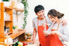 Young Asian lovely couple cooking together at home kitchen, wear red apron making lunch meal. Girl taste soup using spoon. Married people lifestyle, love stock photography