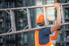 Young Asian maintenance worker carrying aluminium ladder. Young Asian maintenance worker with orange safety helmet and vest carrying aluminium step ladder at Stock Image