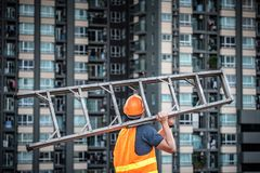 Young Asian maintenance worker carrying aluminium ladder. Young Asian maintenance worker with orange safety helmet and vest carrying aluminium step ladder at Royalty Free Stock Photos