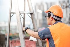 Young Asian maintenance worker carrying aluminium ladder. Young Asian maintenance worker with orange safety helmet and vest carrying aluminium step ladder at Stock Photo