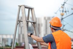 Young Asian maintenance worker holding aluminium ladder. Young Asian maintenance worker with orange safety helmet and vest holding aluminium step ladder at Royalty Free Stock Photo