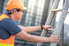 Young Asian maintenance worker man carrying aluminium ladder. Young Asian maintenance worker man with orange safety helmet and vest carrying aluminium step Royalty Free Stock Image
