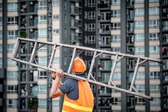 Young Asian maintenance worker man carrying aluminium ladder. Young Asian maintenance worker man with orange safety helmet and vest carrying aluminium step Stock Photography