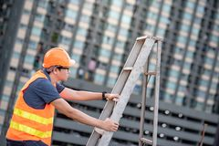 Young Asian maintenance worker man carrying aluminium ladder. Young Asian maintenance worker man with orange safety helmet and vest carrying aluminium step Stock Photos