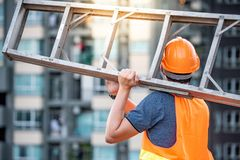 Young Asian maintenance worker man carrying aluminium ladder. Young Asian maintenance worker man with orange safety helmet and vest carrying aluminium step Royalty Free Stock Photos
