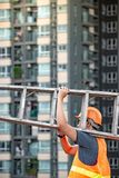 Young Asian maintenance worker man carrying aluminium ladder. Young Asian maintenance worker man with orange safety helmet and vest carrying aluminium step Royalty Free Stock Photo