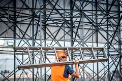 Young Asian maintenance worker carrying aluminium ladder. Young Asian maintenance worker with orange safety helmet and vest carrying aluminium step ladder at Royalty Free Stock Image