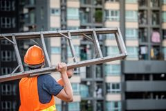 Young Asian maintenance worker carrying aluminium ladder. Young Asian maintenance worker with orange safety helmet and vest carrying aluminium step ladder at Royalty Free Stock Photo