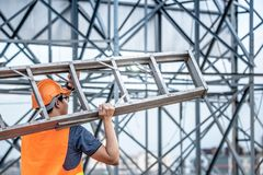 Young Asian maintenance worker carrying aluminium ladder. Young Asian maintenance worker with orange safety helmet and vest carrying aluminium step ladder at Royalty Free Stock Images
