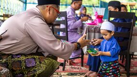Free Young Asian Malay Kids Getting A Envelope Of Money Or Duit Raya During The Hari Raya Aidilfitri Celebration Stock Photos - 179488683