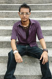 Young Asian Male. Handsome young Asian male with spectacles sitting on stairs Stock Photography
