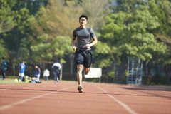 Young asian male athlete running on track. Young asian man male athlete running training exercising on track Stock Image